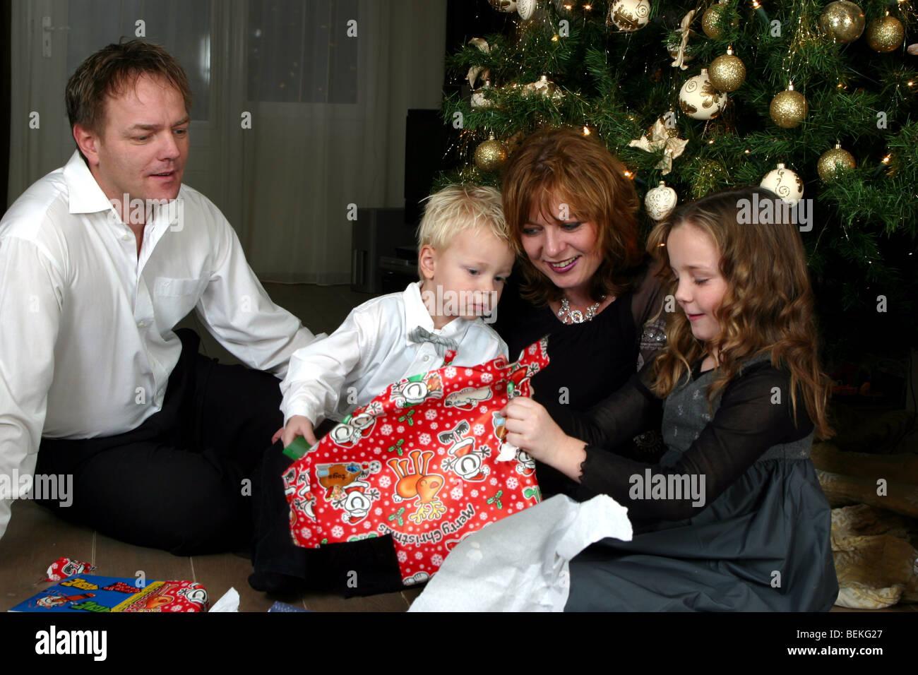 Junge Familie Gerät auspacken Weihnachtsgeschenke vor Baum, die ...