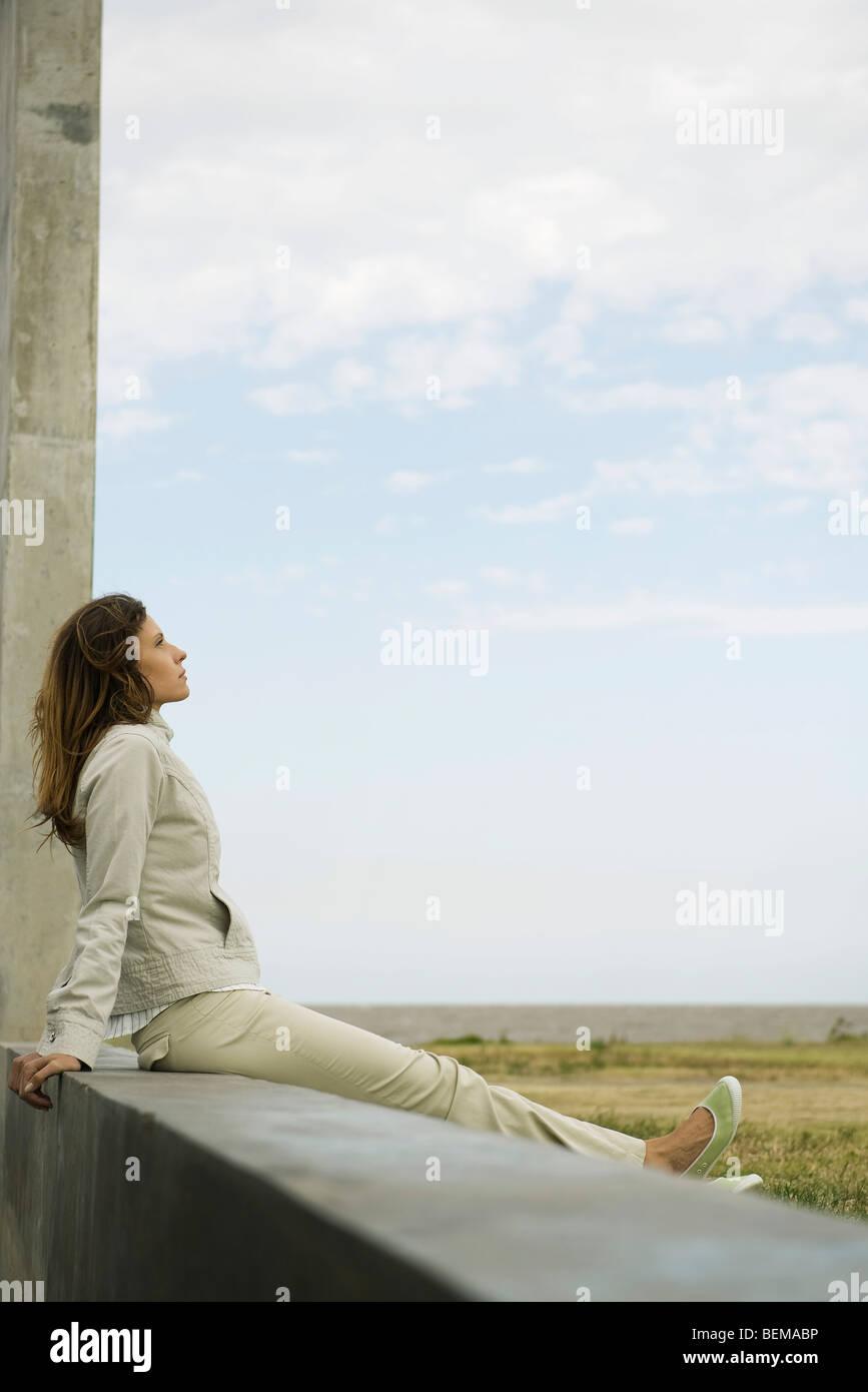 Frau sitzt auf einem Felsvorsprung betrachten, Tagträumen Stockbild