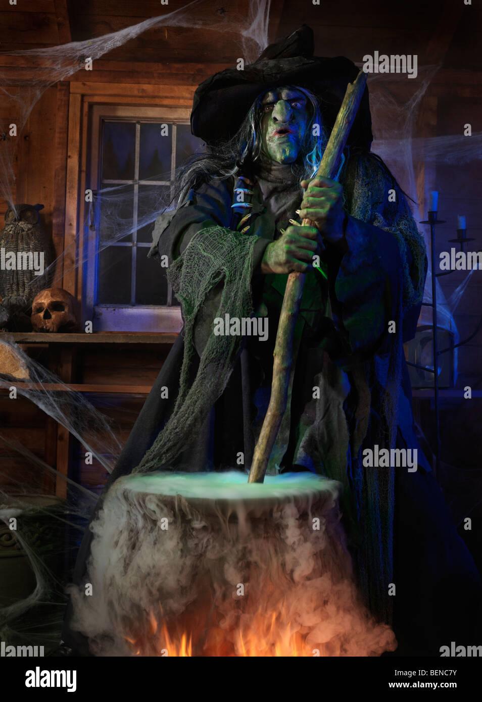Gruselige alte Hexe rühren trank in einem Kessel in ihrer Kabine zu Halloween Stockbild