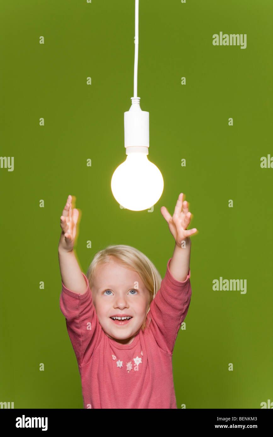 Kleines Mädchen für hängende Glühlampe erreichen Stockbild