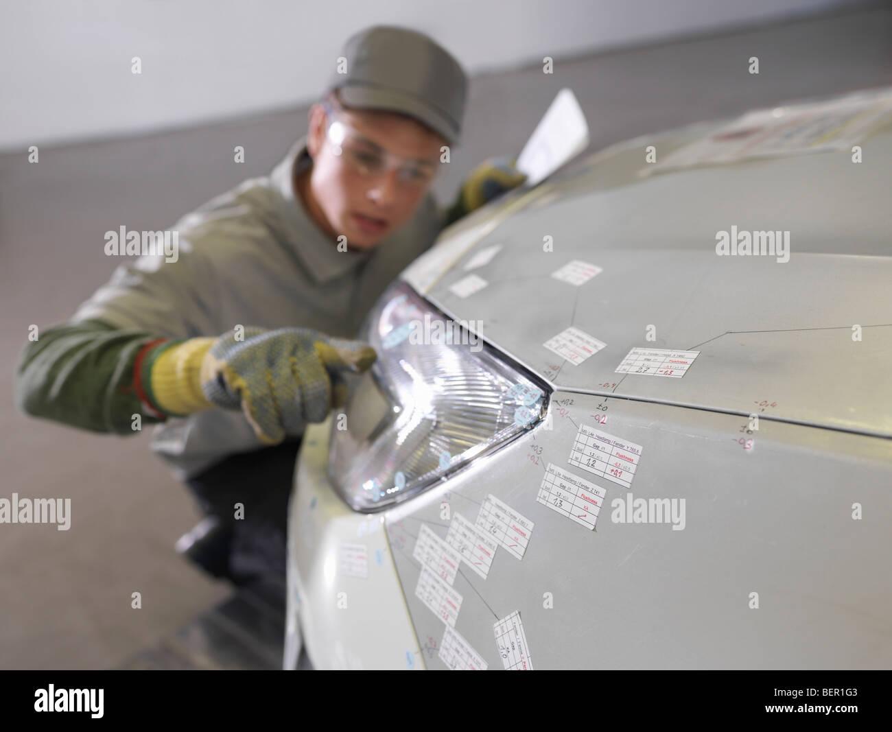 Arbeiter Scheinwerfer am Auto Inspektion Stockbild