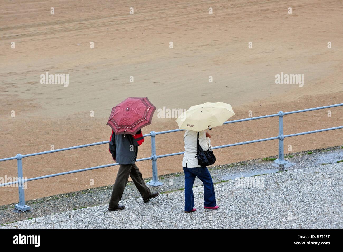 Touristen mit Sonnenschirmen zu Fuß auf der Promenade entlang Nordseestrand im Badeort an einem regnerischen Stockbild