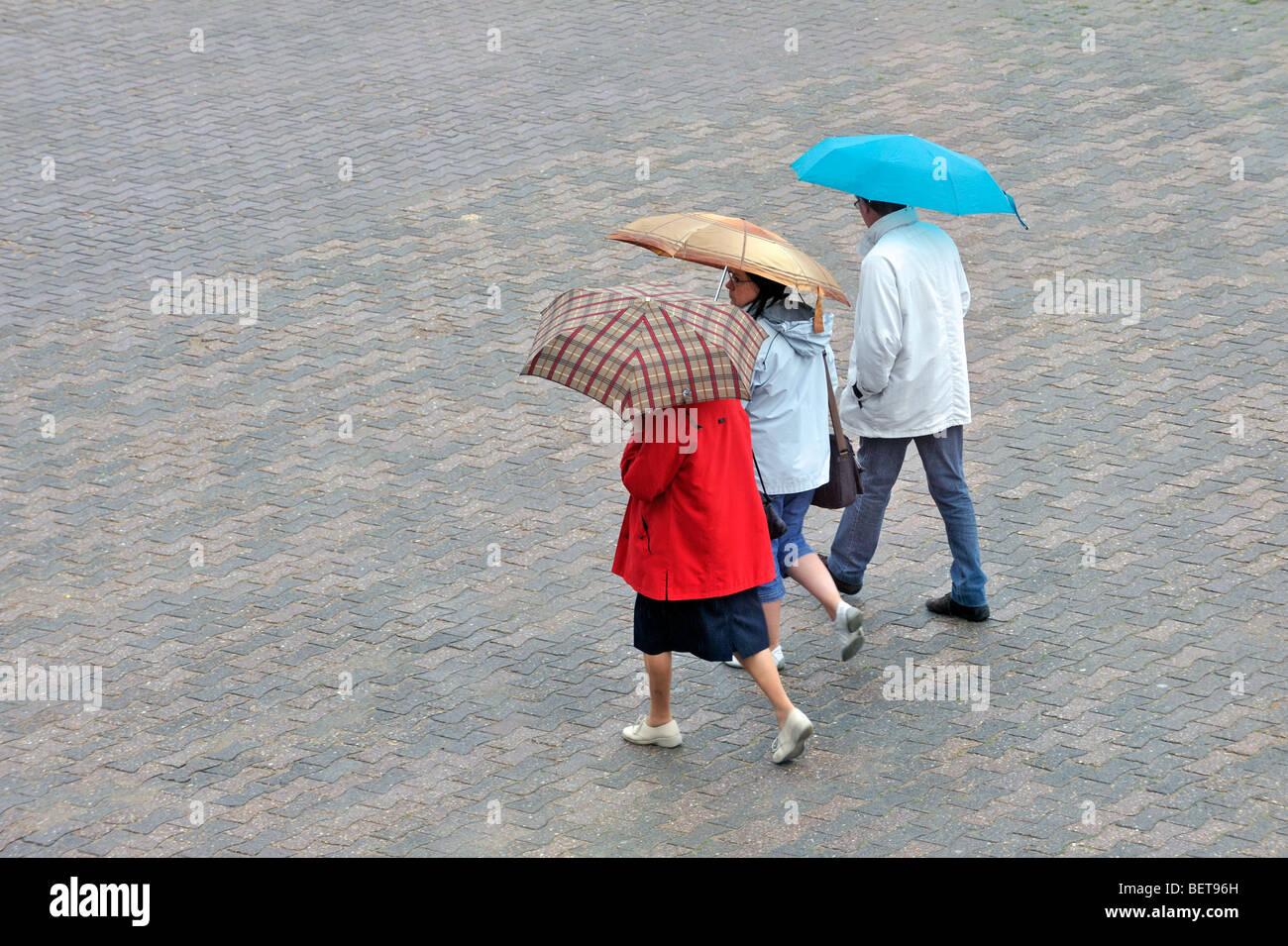 Touristen mit Regenschirme und Regenmäntel an regnerischen Tag im Regen im Badeort an der Küste entlang Stockbild