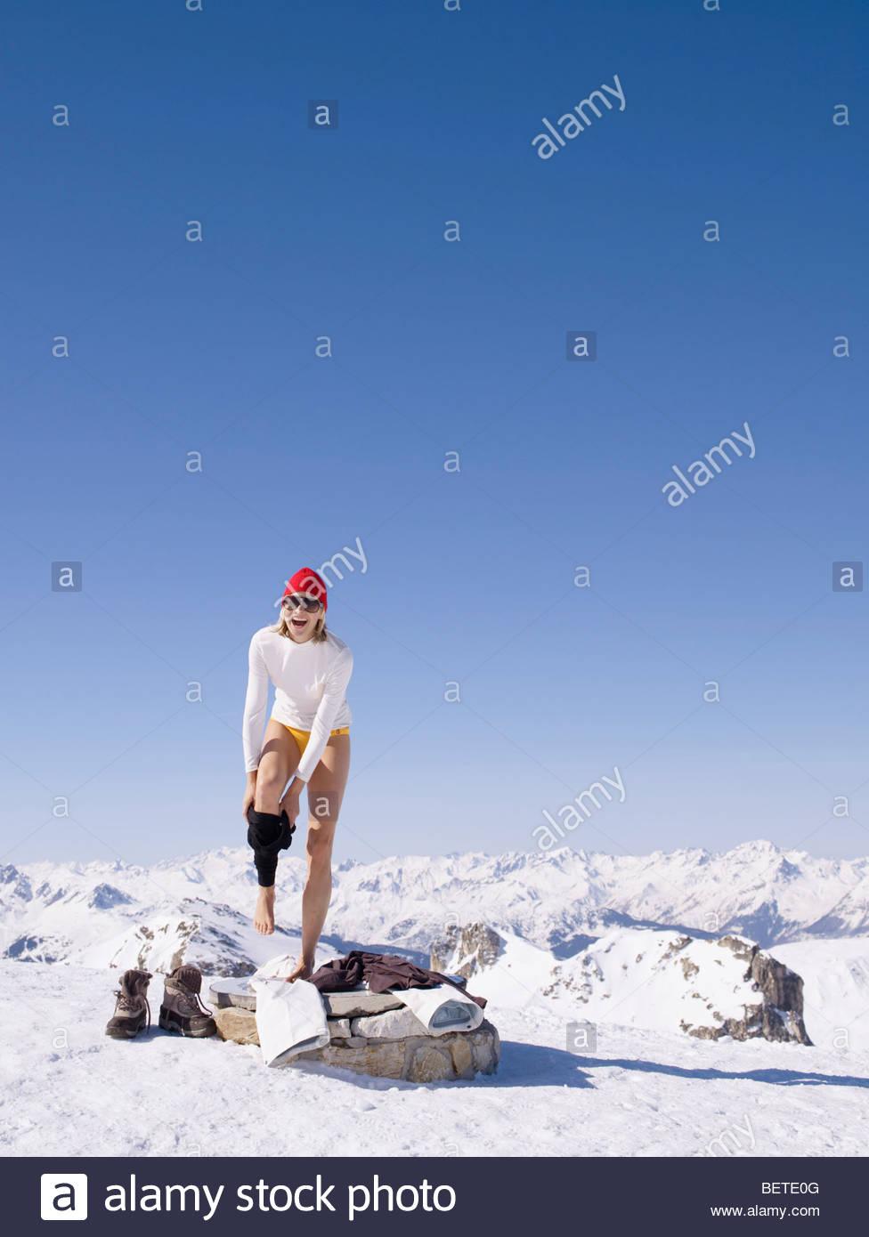 Frau Ausziehen auf Berggipfel Stockbild
