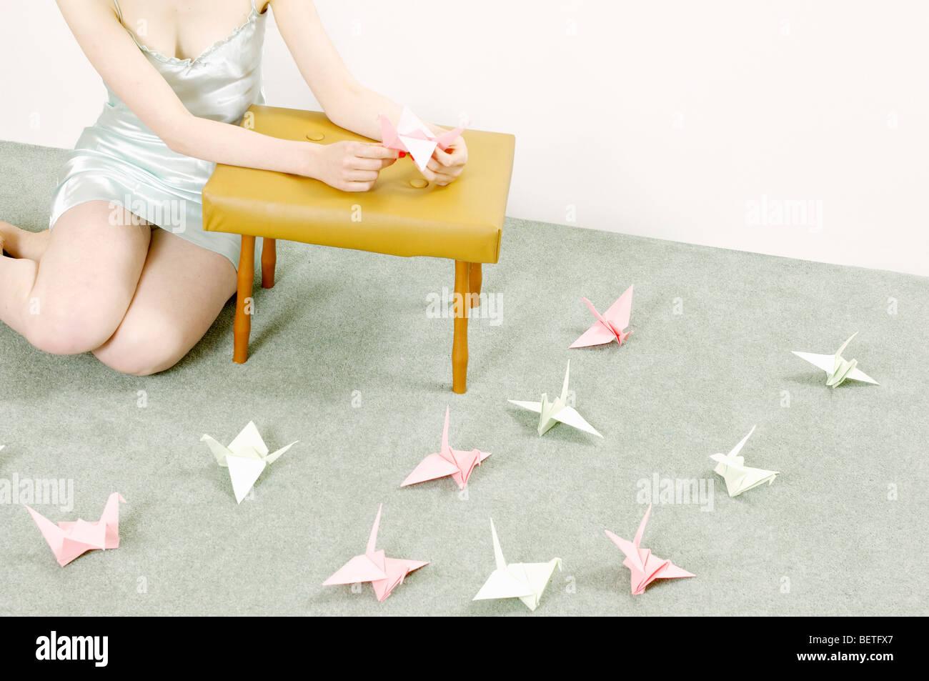 Frau macht Origami Schwäne Stockbild