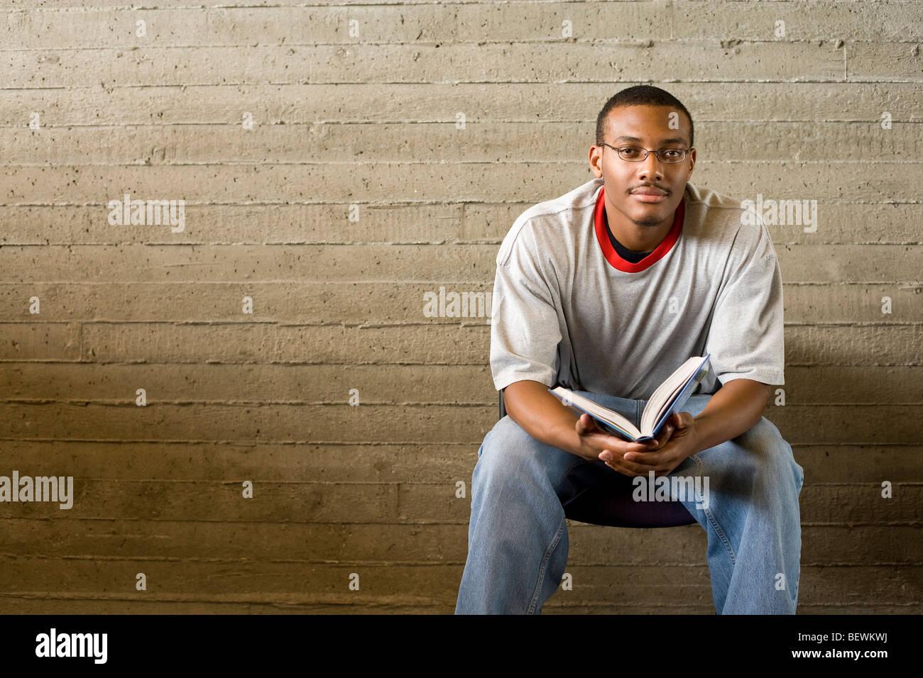Junger Mann liest und Studien in einer Bibliothek Stockbild