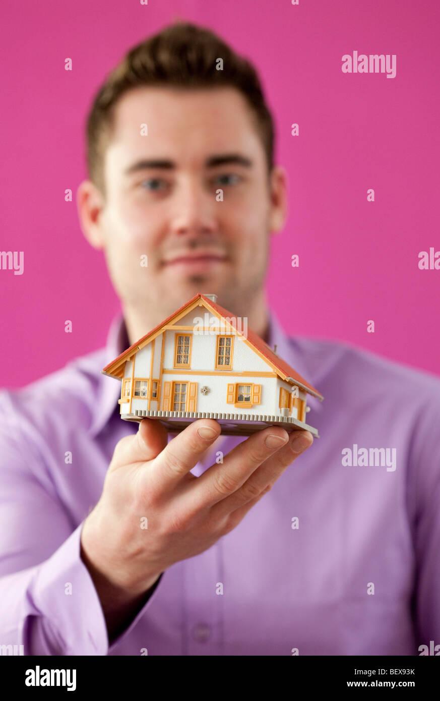 Junger Mann hält ein kleines Haus. Stockbild