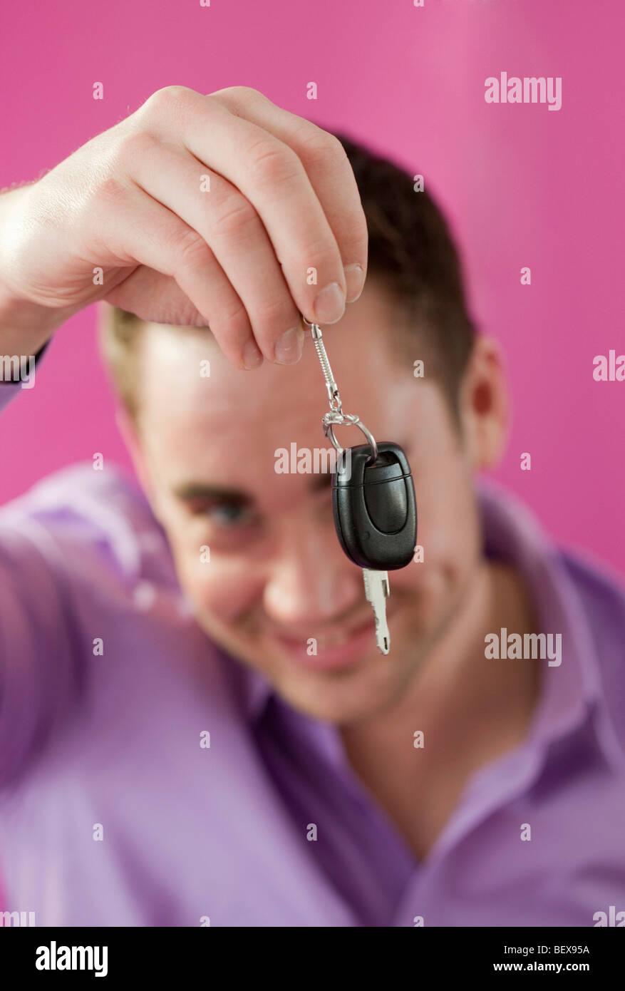 Junger Mann hält einen Autoschlüssel. Stockbild