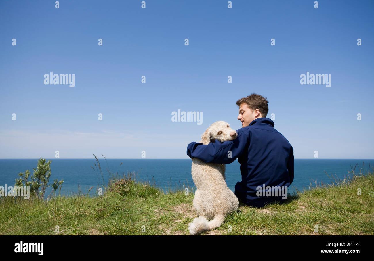 Ein Mann mit seinen Arm um ein Hund sitzt am Meer Stockbild