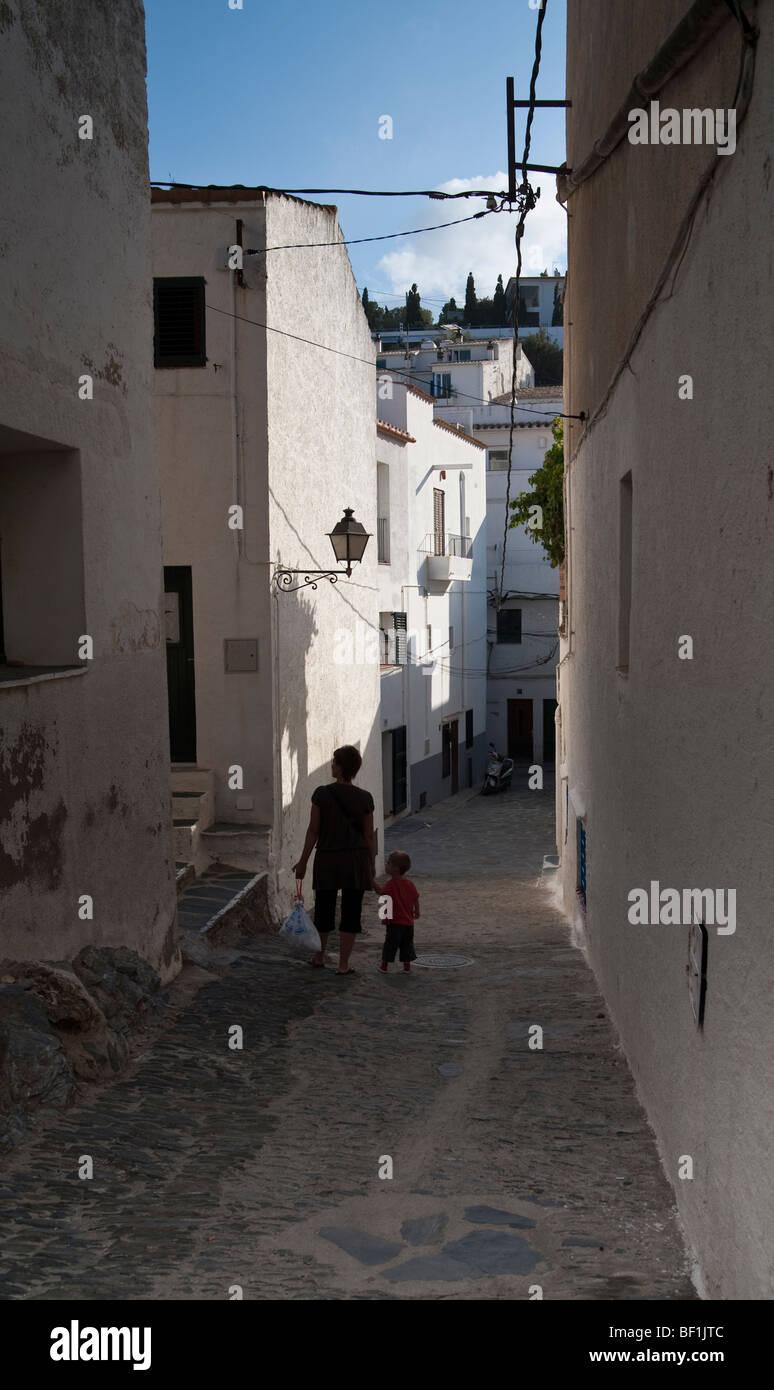 Eine Mutter geht ihr Kind auf den gepflasterten Gassen von Nordspanien, eine späte Sonne trifft die alte weiße Stockbild
