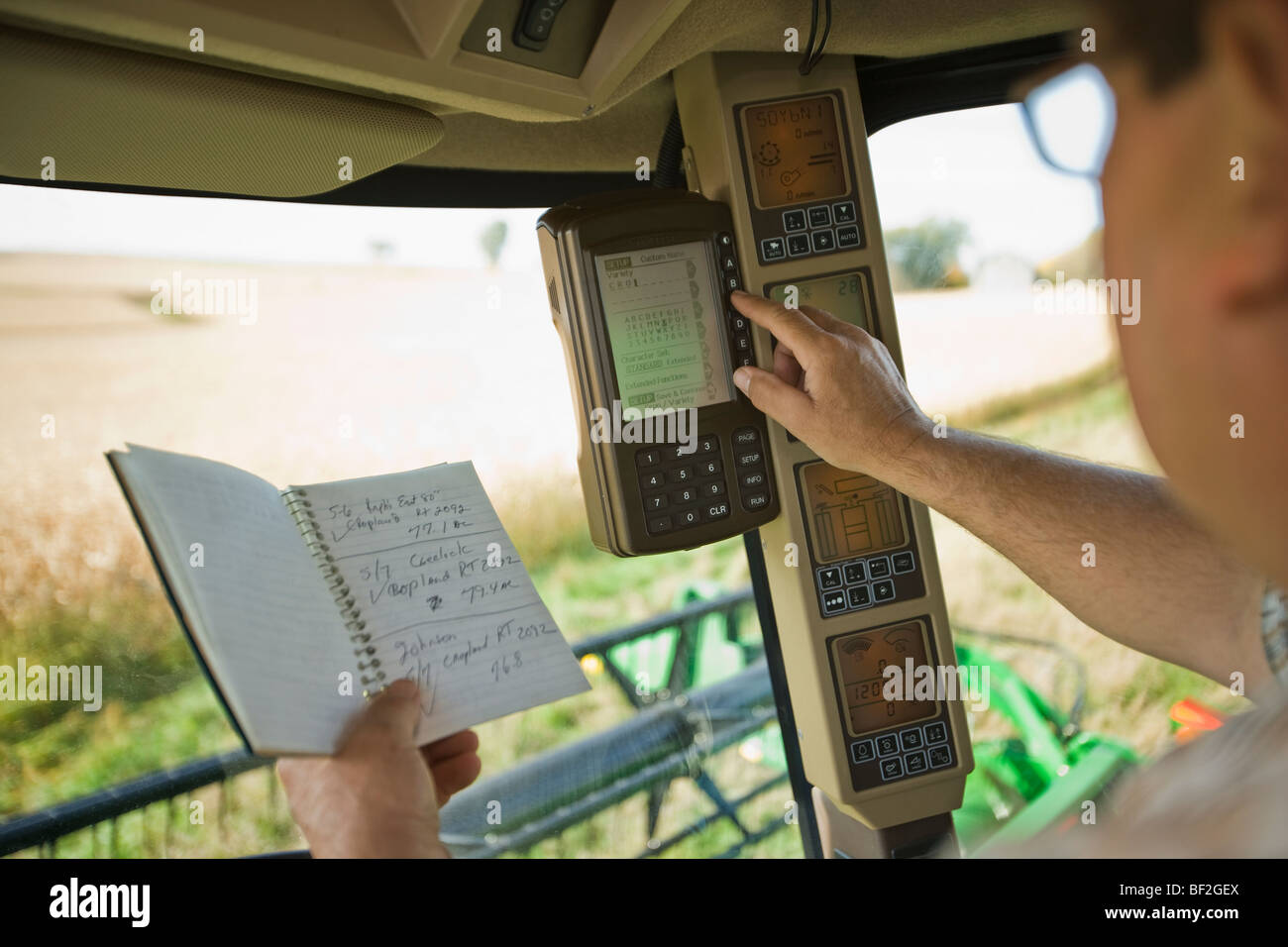 Ein Bauer Eingänge Daten in den Rendite-Monitor in der Kabine von einem Mähdrescher bei der Soja-Ernte Stockbild