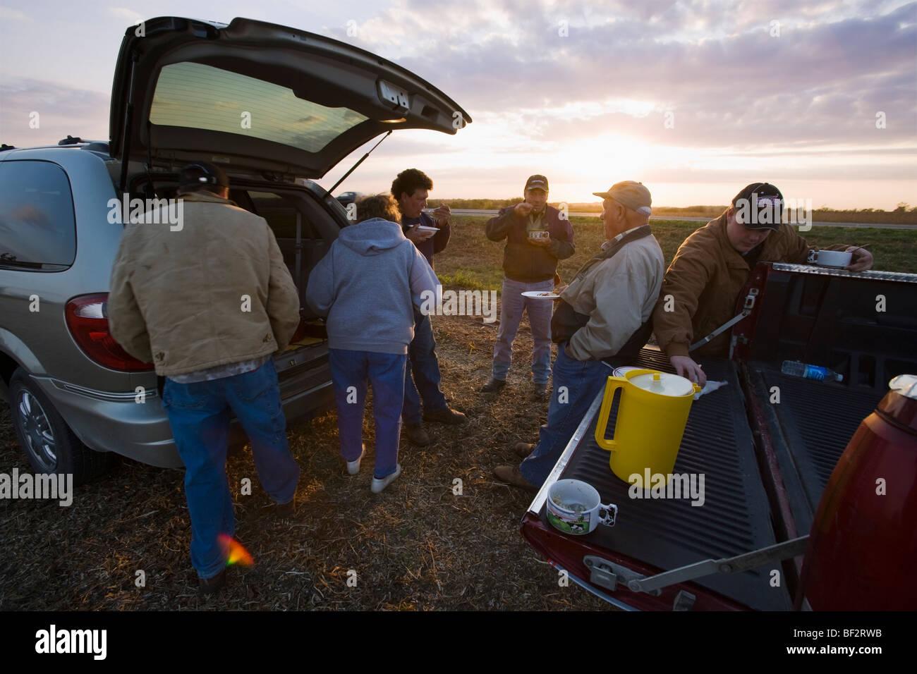 Eine Farmerfamilie teilt eine Mahlzeit zusammen im Feld während der langen Tage der Herbsternte / in der Nähe Stockbild