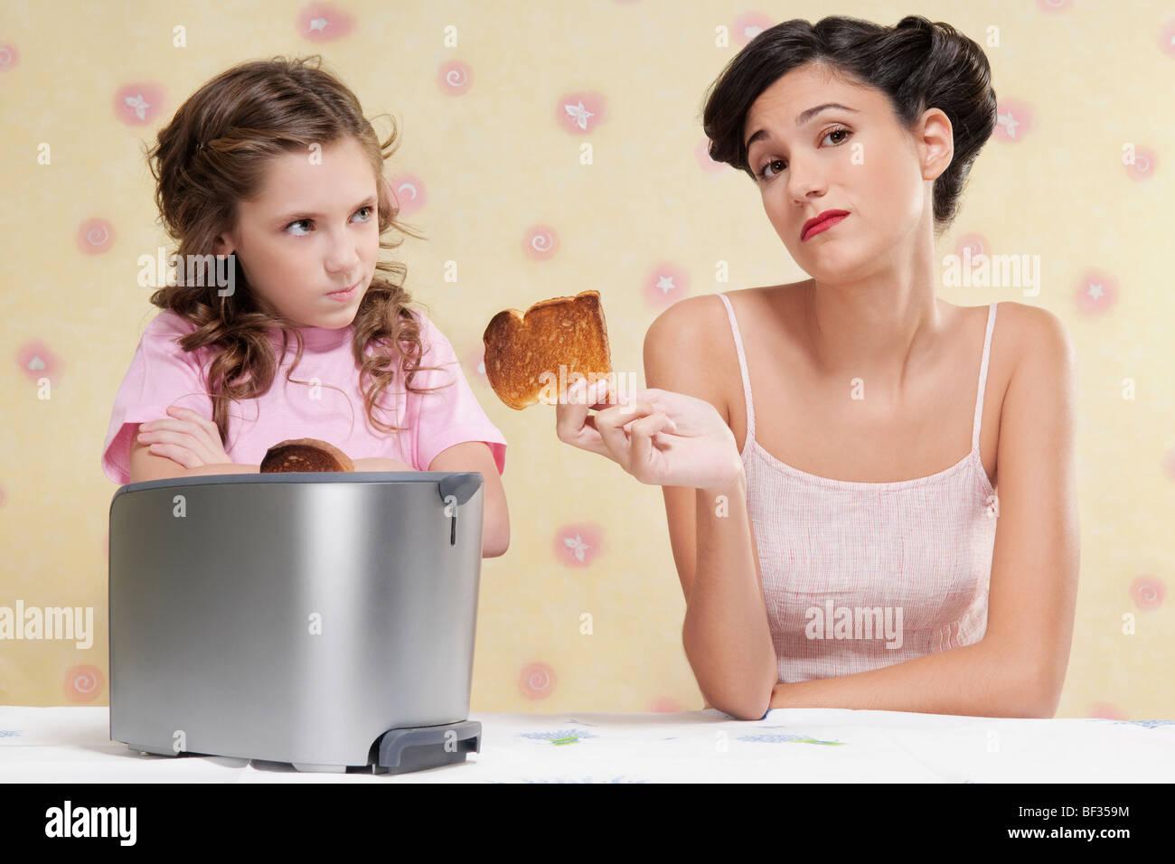 Geben ihrer Tochter einen verbrannten Toast Frau Stockbild