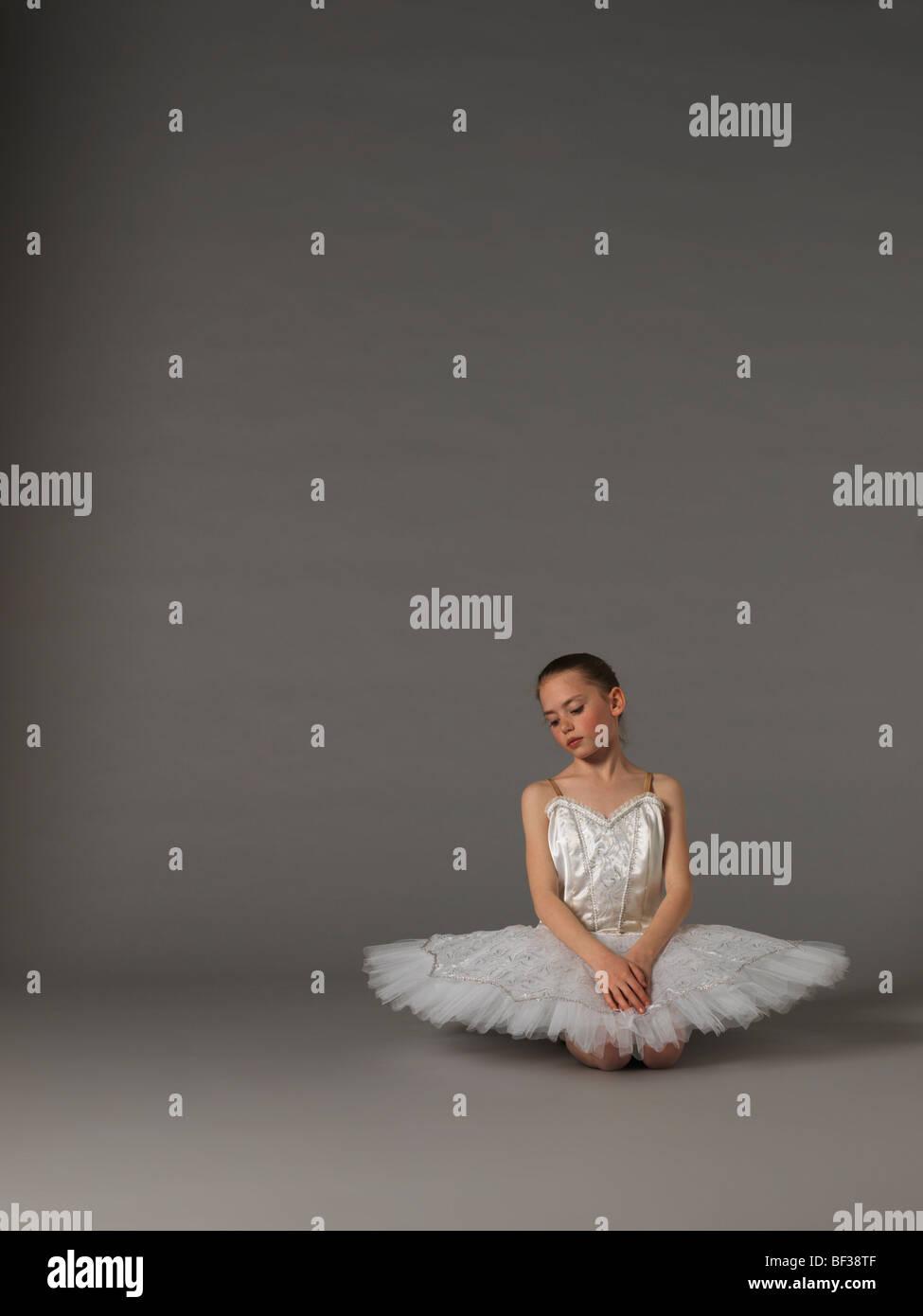Mädchen in weißen Tutu kniend. Stockbild