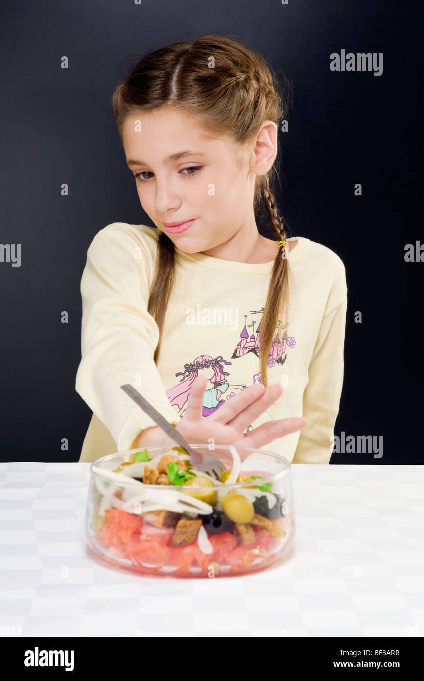 Nahaufnahme eines Mädchens schob eine Schüssel mit Salat entfernt Stockbild