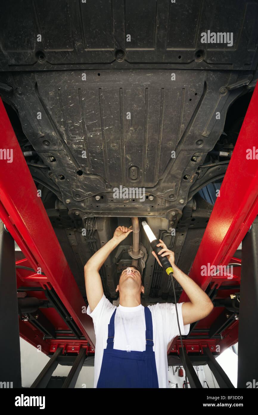 Mechaniker, stehend unter Automotor und Lampe halten. Textfreiraum ...
