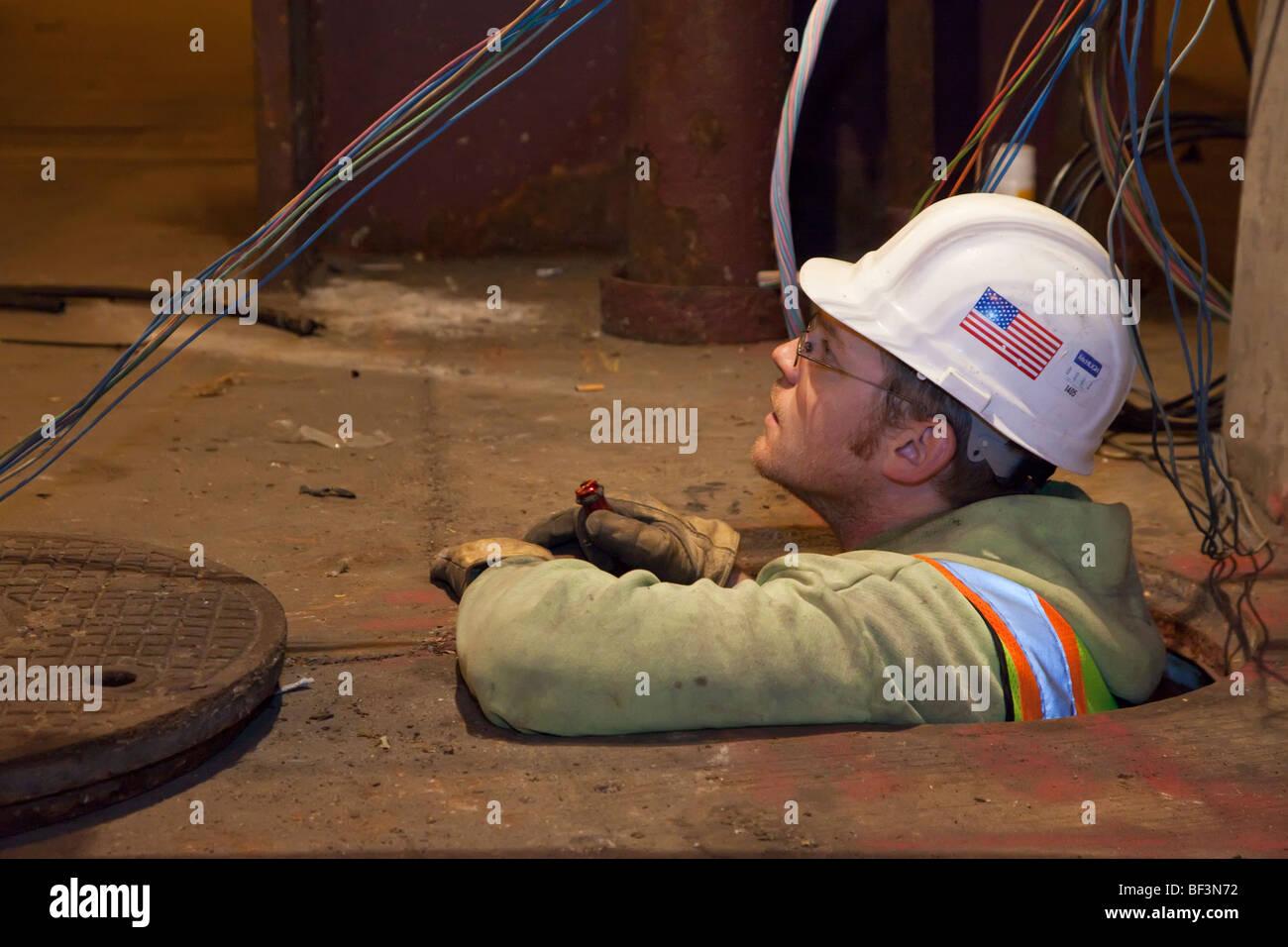 Chicago, Illinois - ein Angestellter im öffentlichen Dienst arbeiten an elektrischen Leitungen in einem Schacht. Stockbild