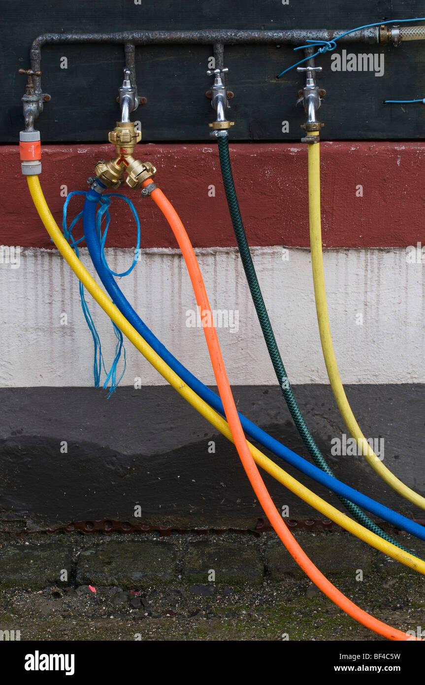 Wasserknappheit, vier undichte Wasserhähne, eines mit einer doppelten Kreuzung und fünf farbige Schläuche Stockbild