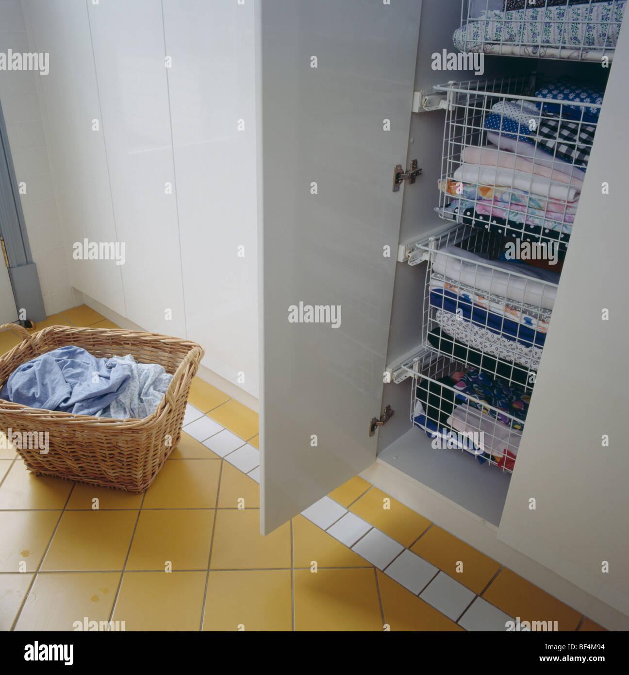 Hauswirtschaftsraum mit Korb Wäsche neben Schrank mit gefalteter ...
