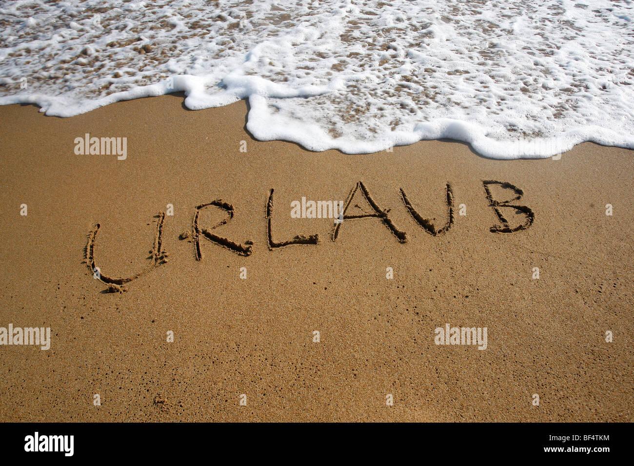 Urlaub, Deutsch für Urlaub, geschrieben in den Sand am Strand, Korfu, Griechenland, Europa Stockbild