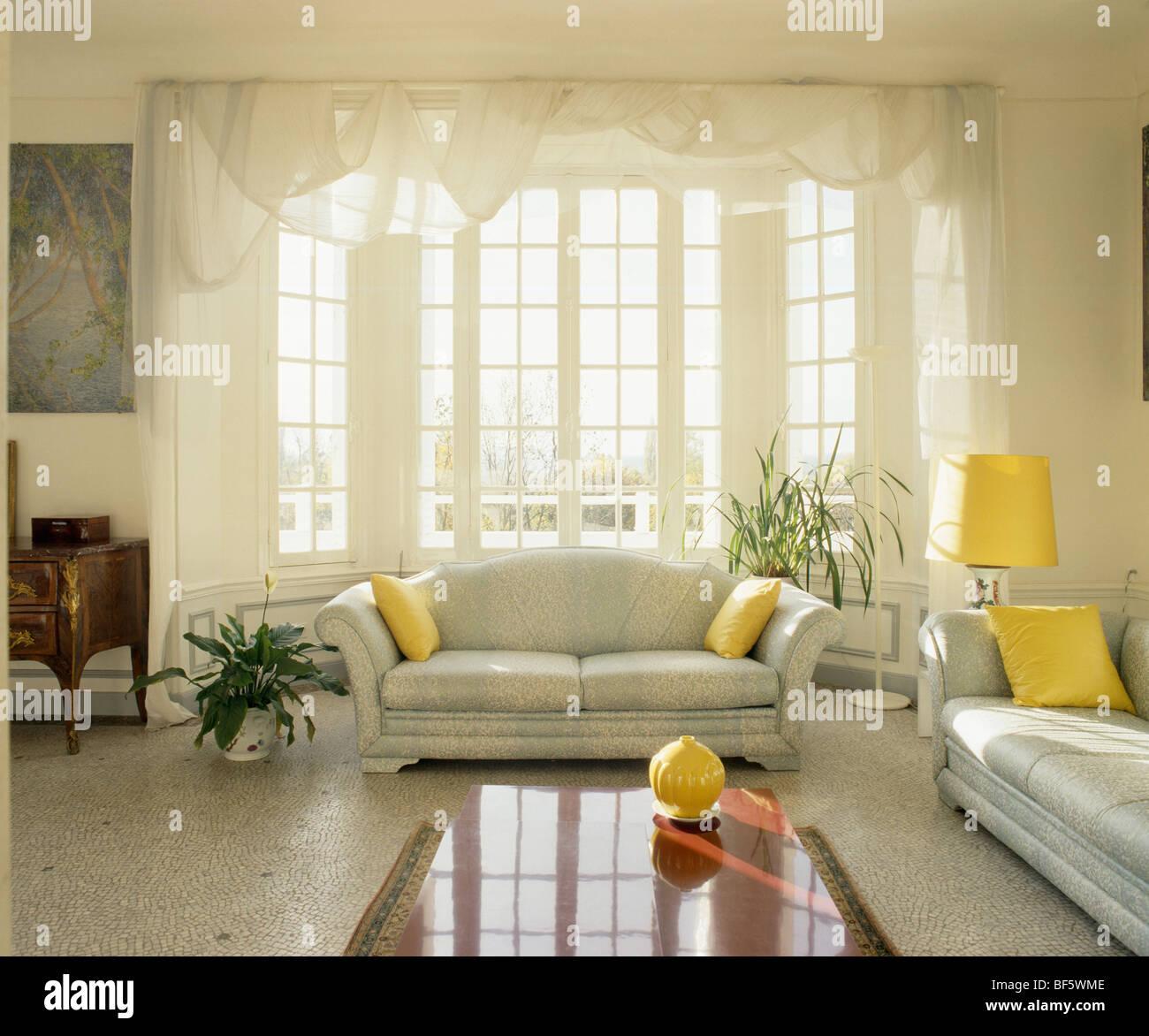Terrazzo-Boden und grau Sofas mit gelben Kissen im traditionellen ...
