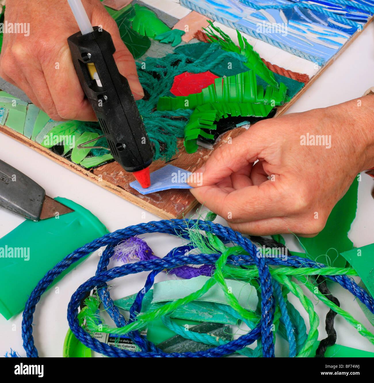 künstler arbeiten mit der klebepistole collage bild zu machen