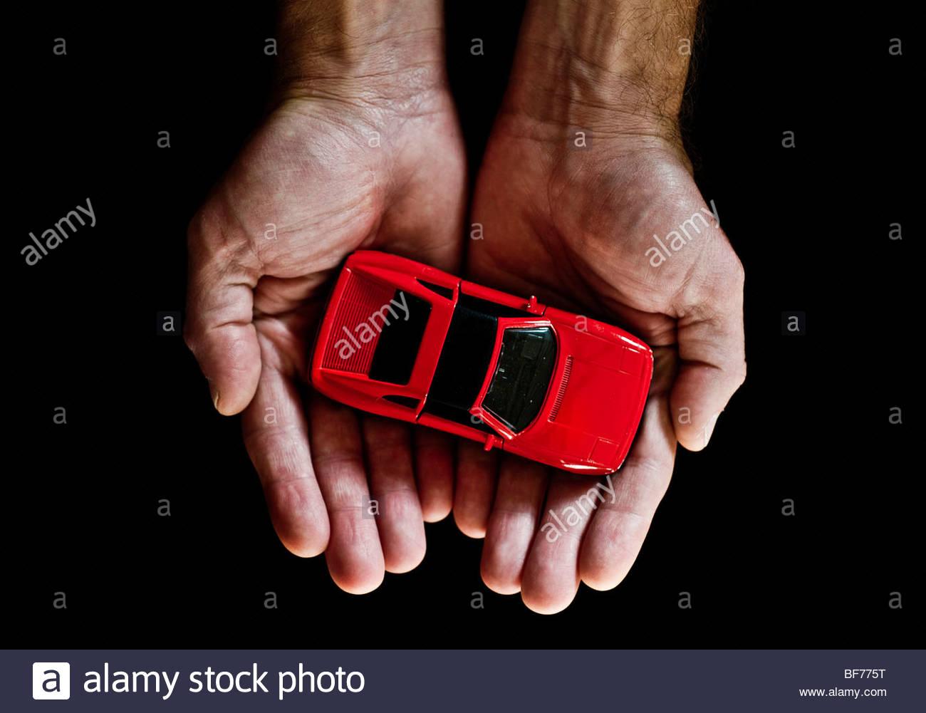 Rotes Auto in Händen Stockbild