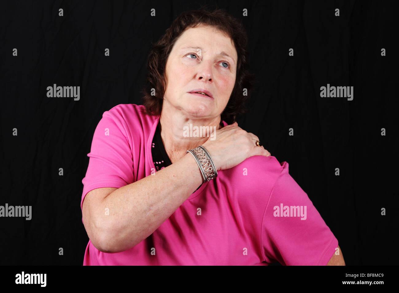 Im späten Mittleren Alter 50er Jahre 50er Jahre Frau hält schmerzende Schulter gemeinsame leiden an schwerer Stockbild