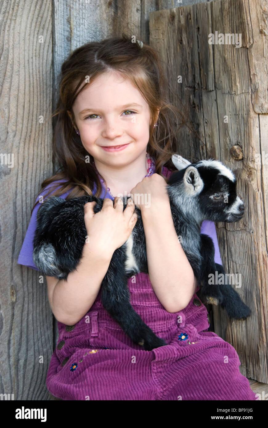 Süße junge Bauernmädchen, hält eine neugeborenes Baby-Ziege. Stockbild