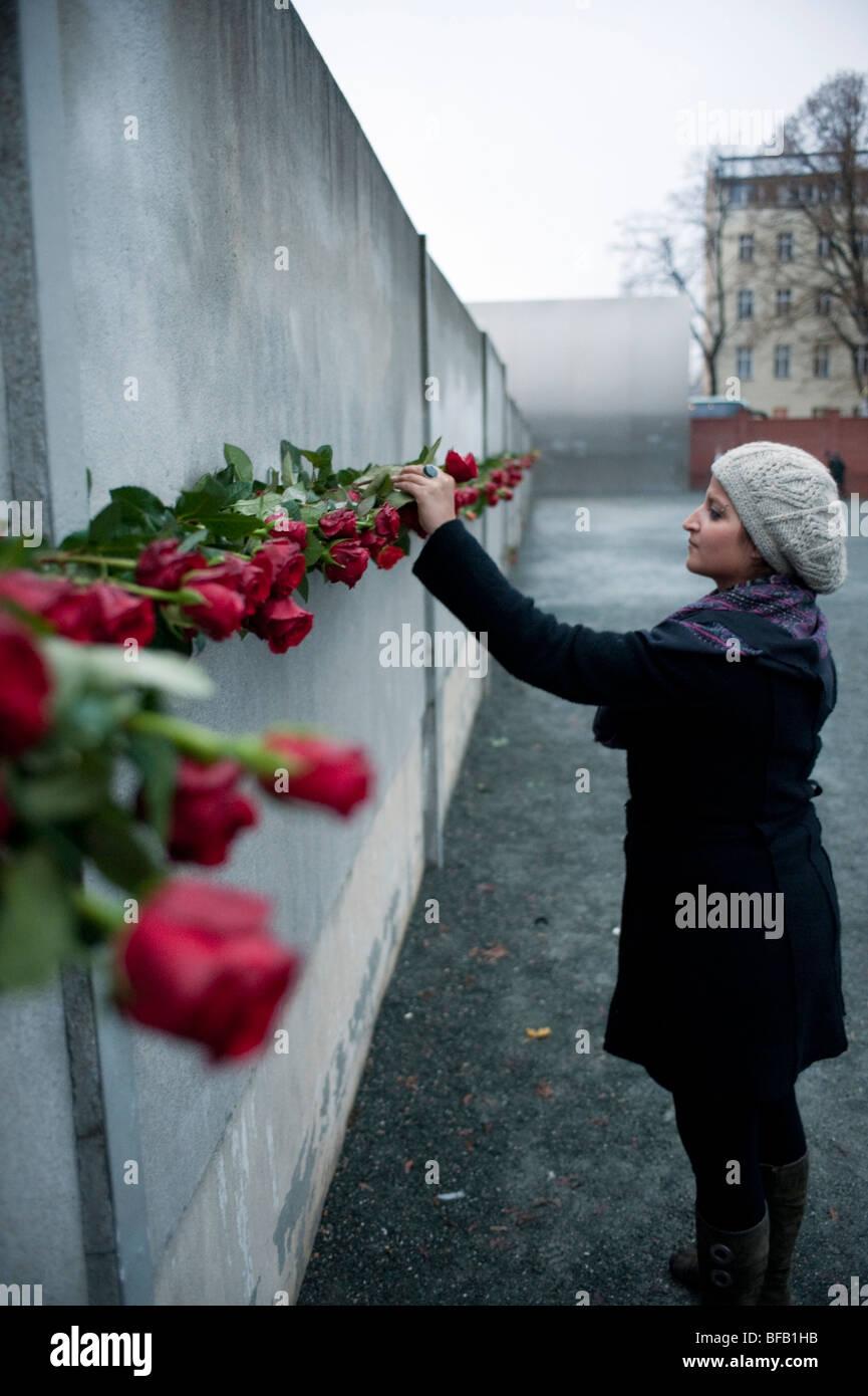 Frau Inverkehrbringen rote rose im Berliner Mauer 20. Jahrestag des Falls der Mauer, um denen zu gedenken, starb Stockbild