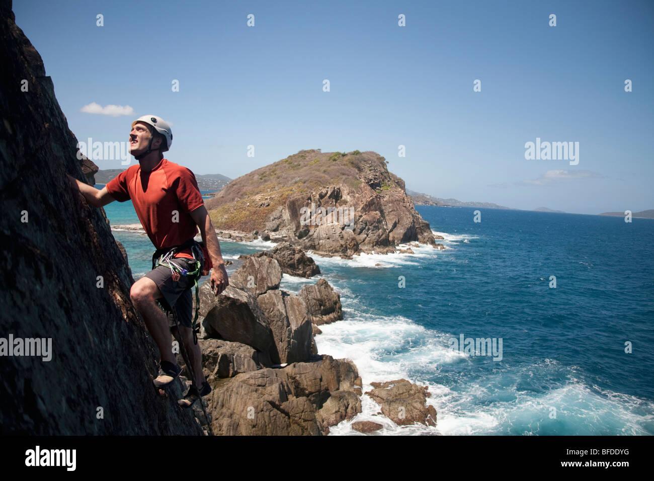 Ein Mann schaut beim Klettern traditionell einer neuen Route entlang einer abgelegenen Cay in den US Virgin Islands. Stockbild