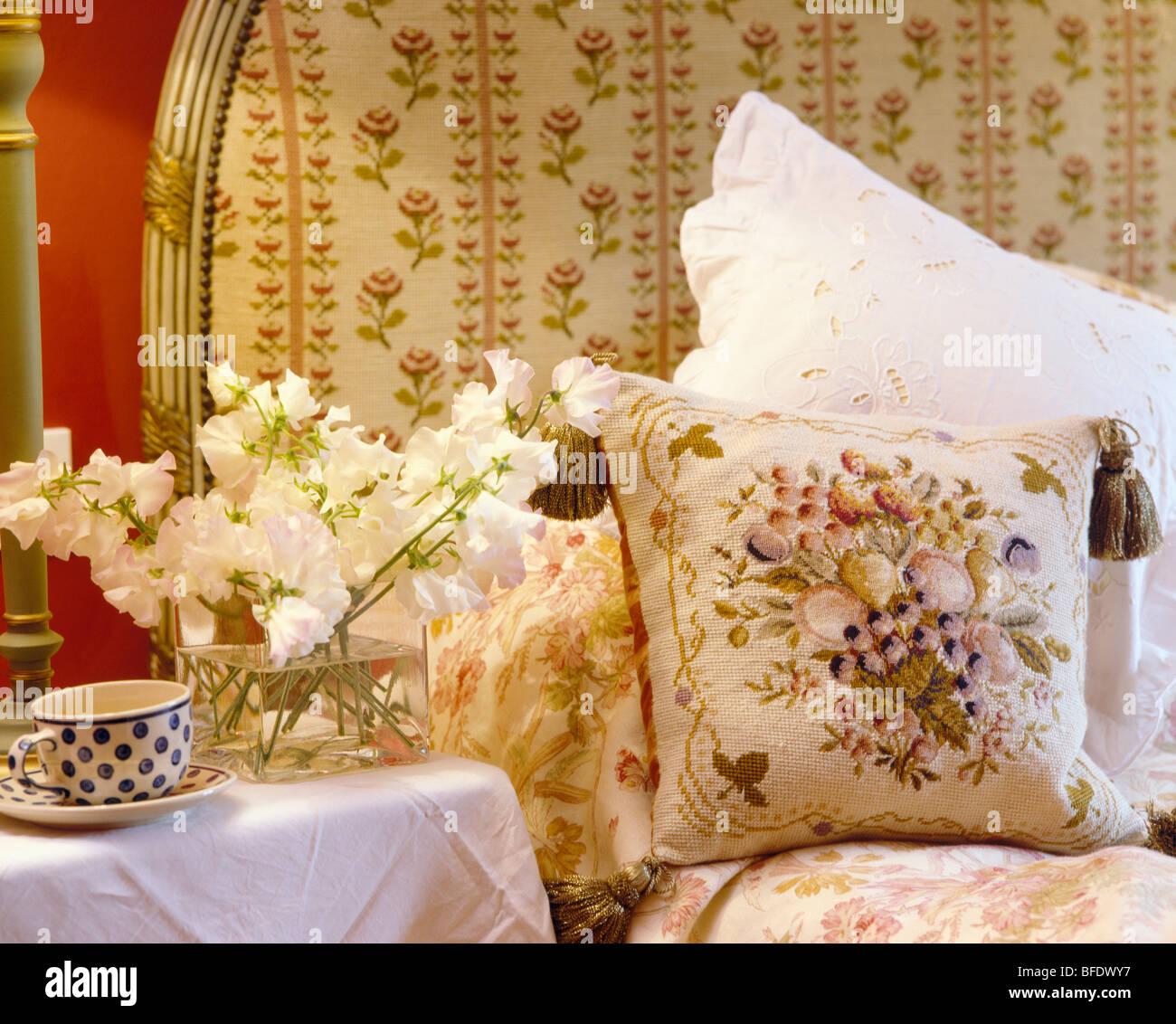 Nahaufnahme Von Zuckererbsen Auf Tisch Neben Bett Mit Gobelin Kissen Und  Weißen Kissen Gegen Gepolsterte Floral Kopfteil