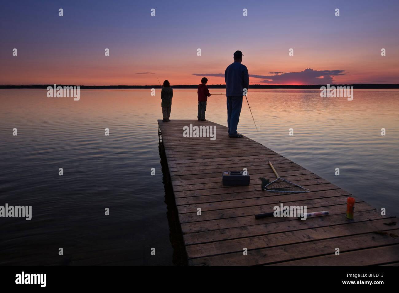 Ein Vater mit seinen beiden Söhnen Angeln am Ende eine Werft am Lake Audy bei Sonnenuntergang, Riding Mountain Stockbild