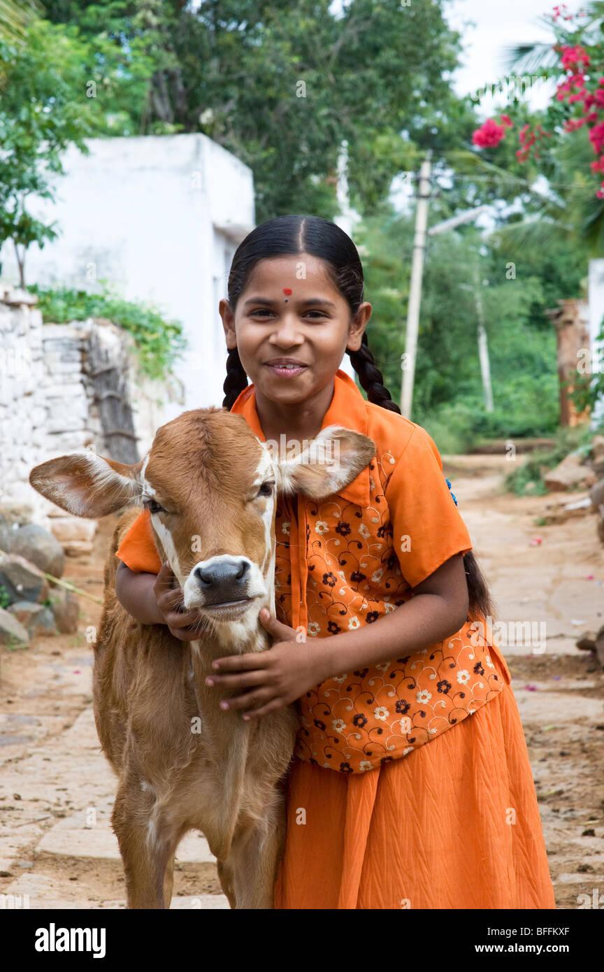 Junge indische Dorfmädchen umarmt eine Kalb in einem indischen Dorf. Andhra Pradesh, Indien Stockbild