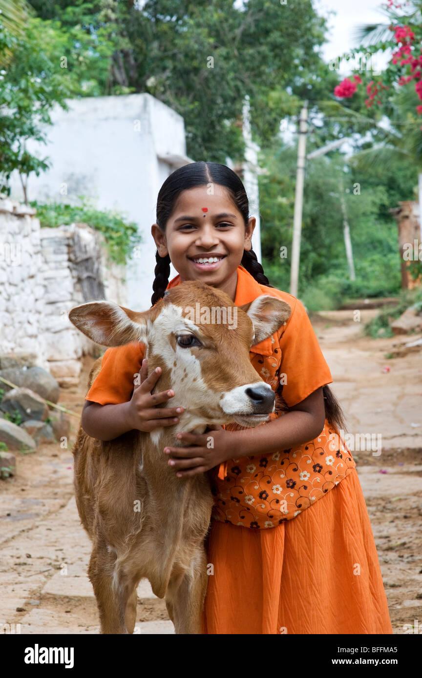 Junge indische Dorf Mädchen umarmt ein Kalb in einer ländlichen indischen Dorf. Andhra Pradesh, Indien Stockbild