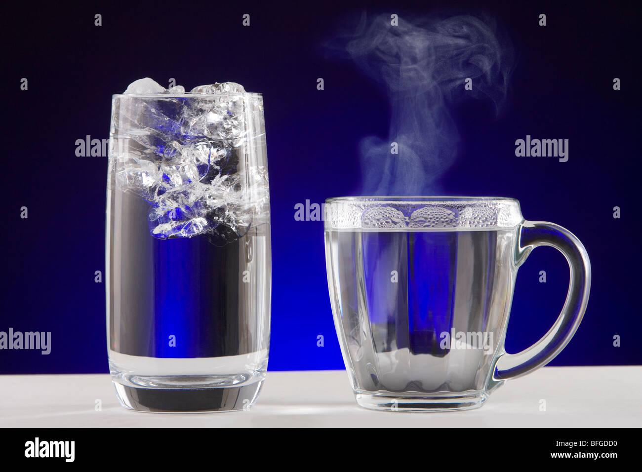 Eis-Dampf-Wasser. Ein Glas Eiswasser und einer Teetasse heiß dampfende Wasser. Stockbild