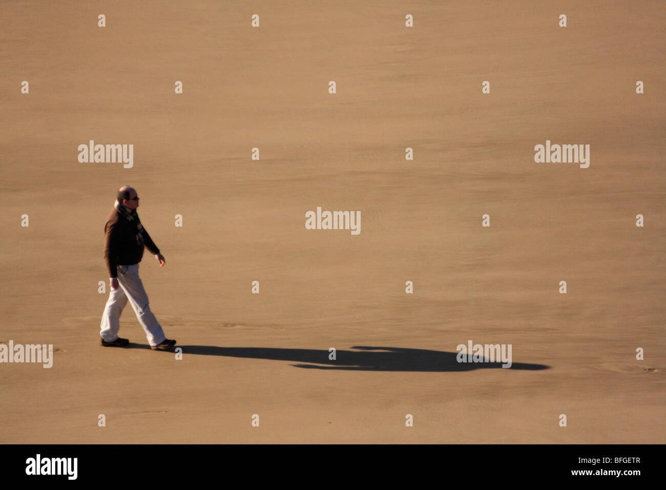Einzigen Mann zu Fuß entlang ein Sandstrand, von oben betrachtet, und wirft einen langen Schatten Stockbild