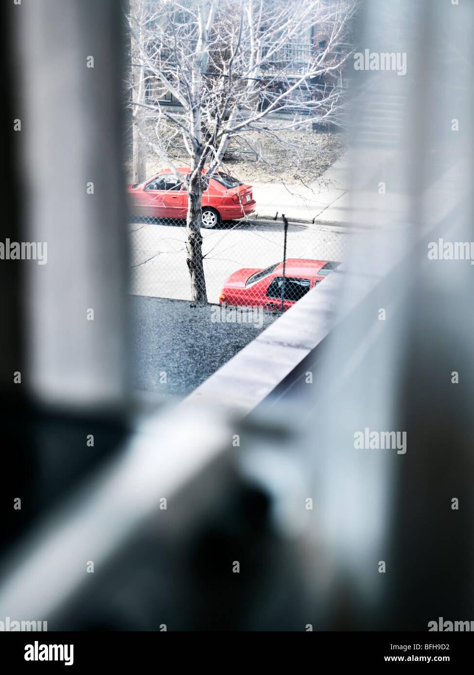 zwei rote Autos oben aus einem verhangenen Fenster gesehen Stockbild