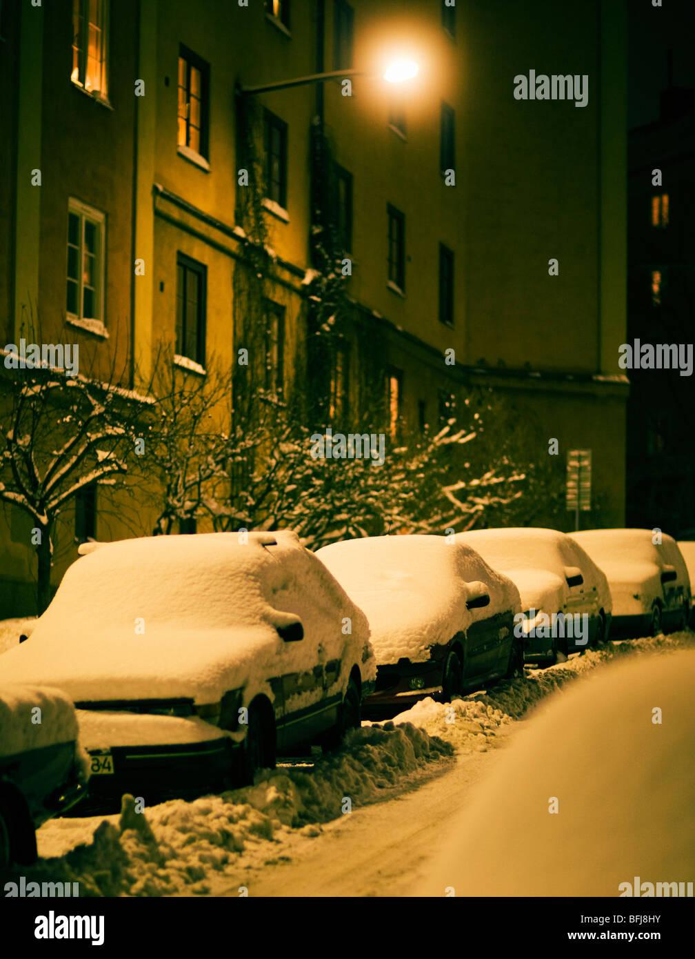 Verschneite Autos auf einer Straße, Schweden. Stockbild