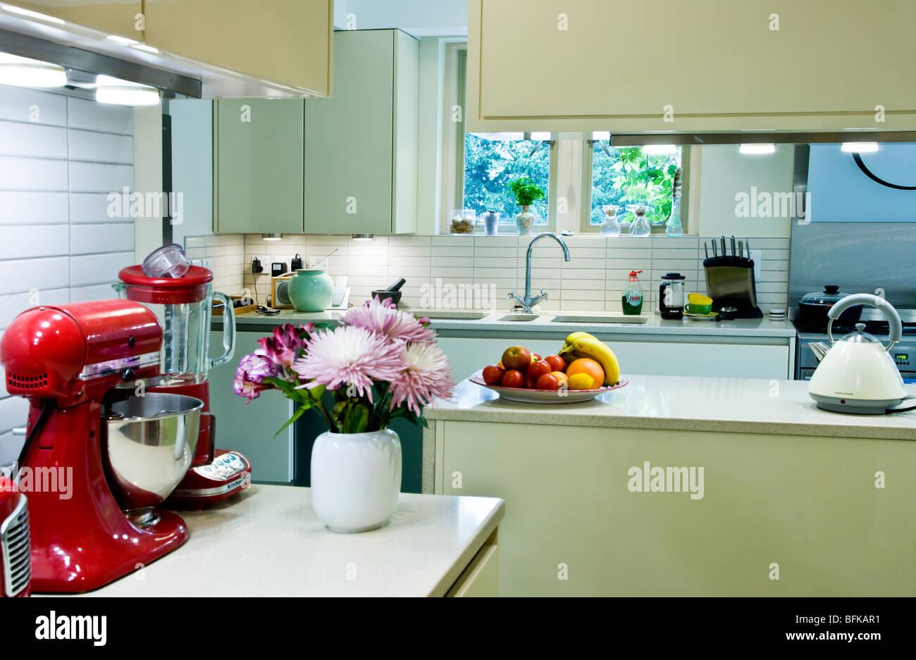 Eine moderne moderne intelligente Küche mit roten Retro-Geräten und Vase mit frischen Blumen Stockbild