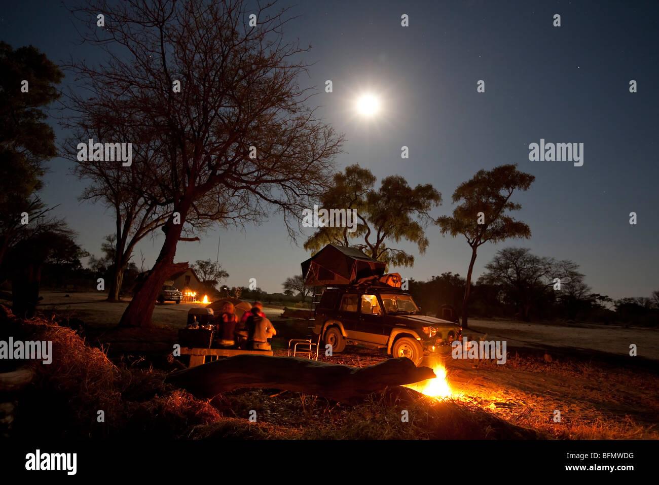 Botswana, Savuti. Eine Familie genießt ihre Mahlzeit durch das Feuer, mit der Expedition 4 x 4 im Hintergrund. Stockbild