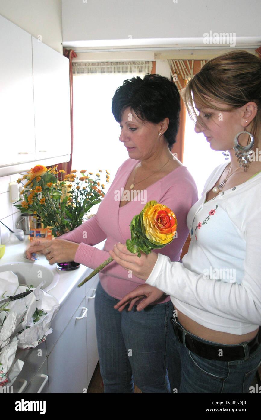 Besucher Geschenk der 20er Jahre Frau und Schwiegermutter Anordnen von Blumen in vase Stockfoto