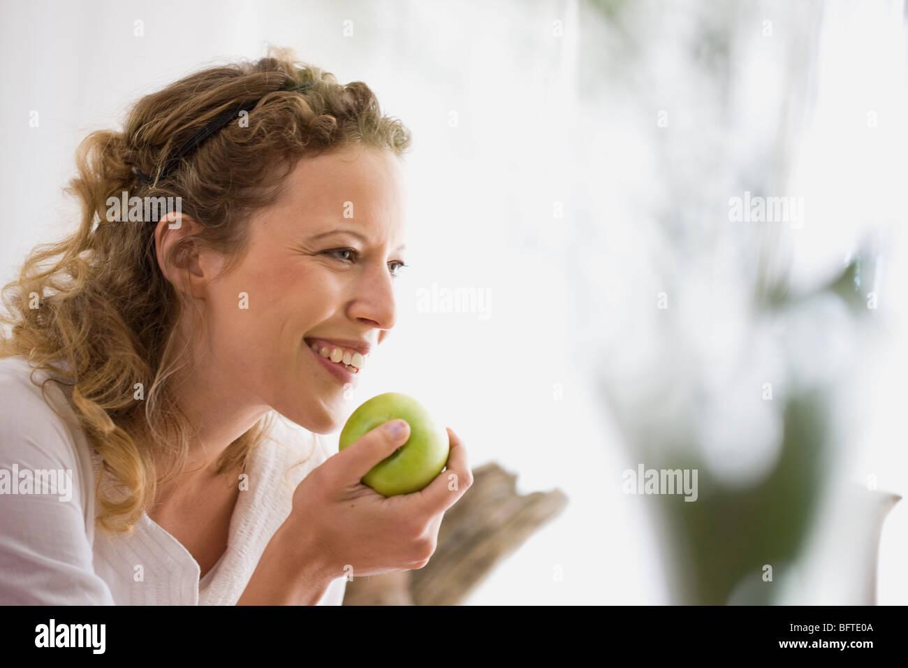 Frau mittleren Alters, die einen Apfel zu essen Stockbild