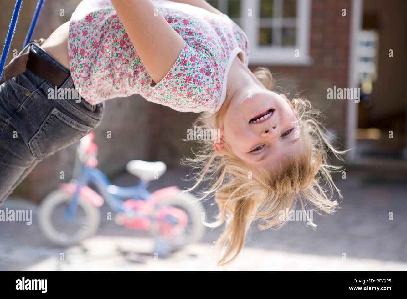 Junges Mädchen auf dem Kopf stehend auf Schaukel Stockbild