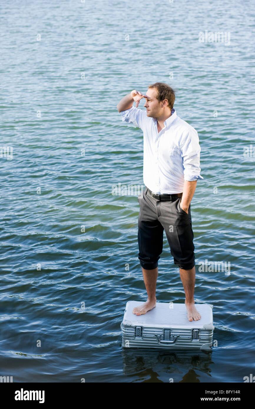 Mann auf schwimmenden Koffer Stockbild