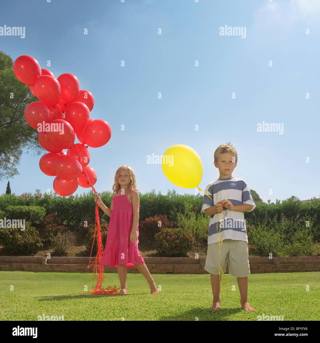 Kleine Kinder halten rote Luftballons Stockbild