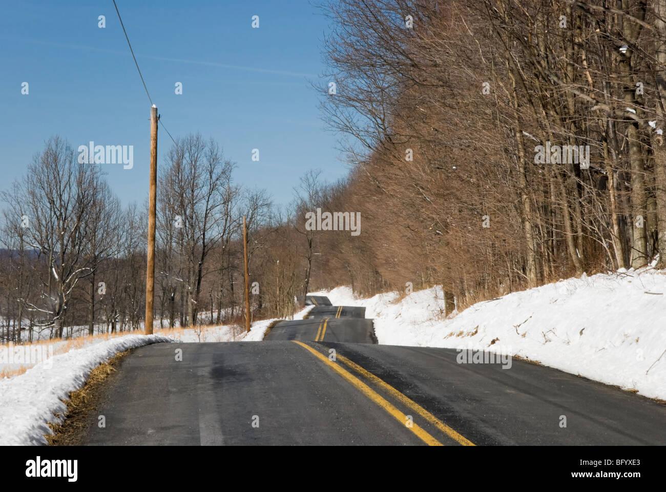 Sanfte Hügel auf einer holprigen zweispurige schwarz Top Straße in ländlichen Pennsylvania, USA. Stockbild
