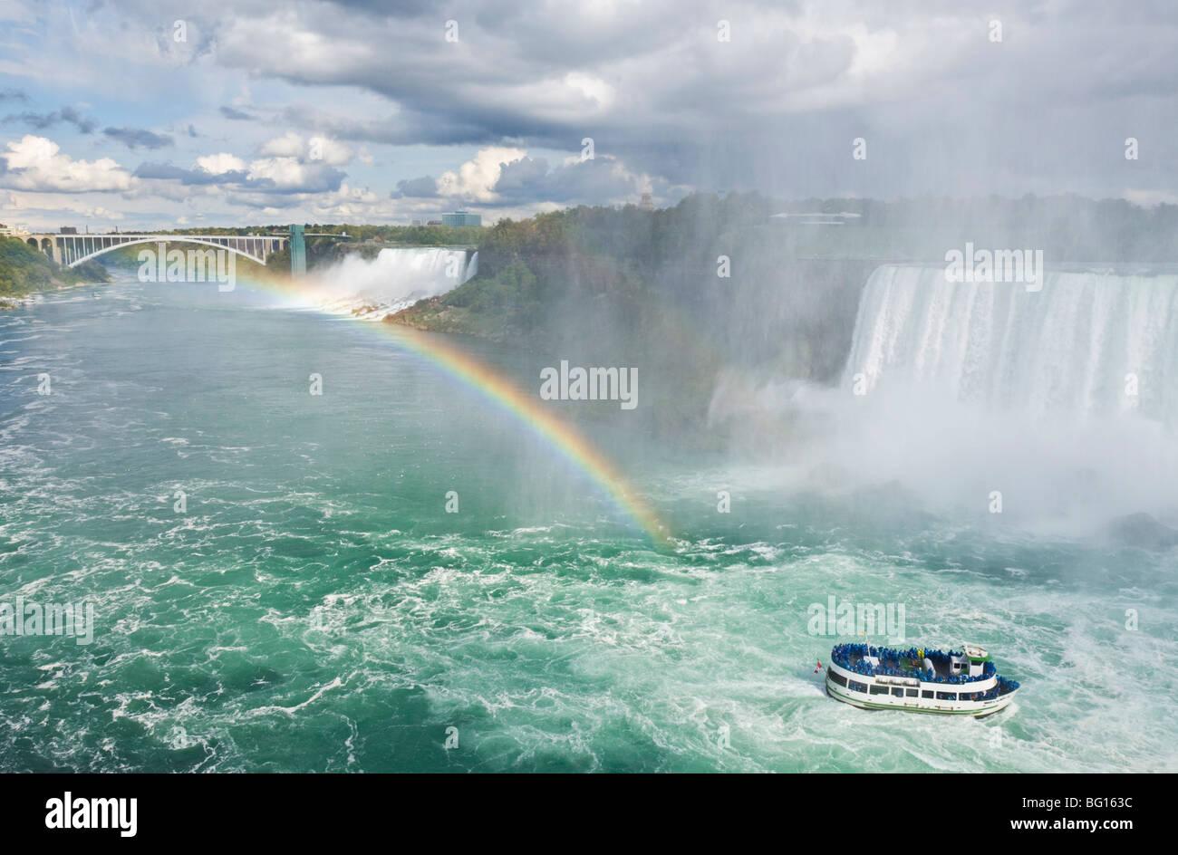 Mädchen der Nebel Tour Ausflug Boot unter den Horseshoe Falls Wasserfall mit Regenbogen am Niagara Falls, Ontario, Stockbild