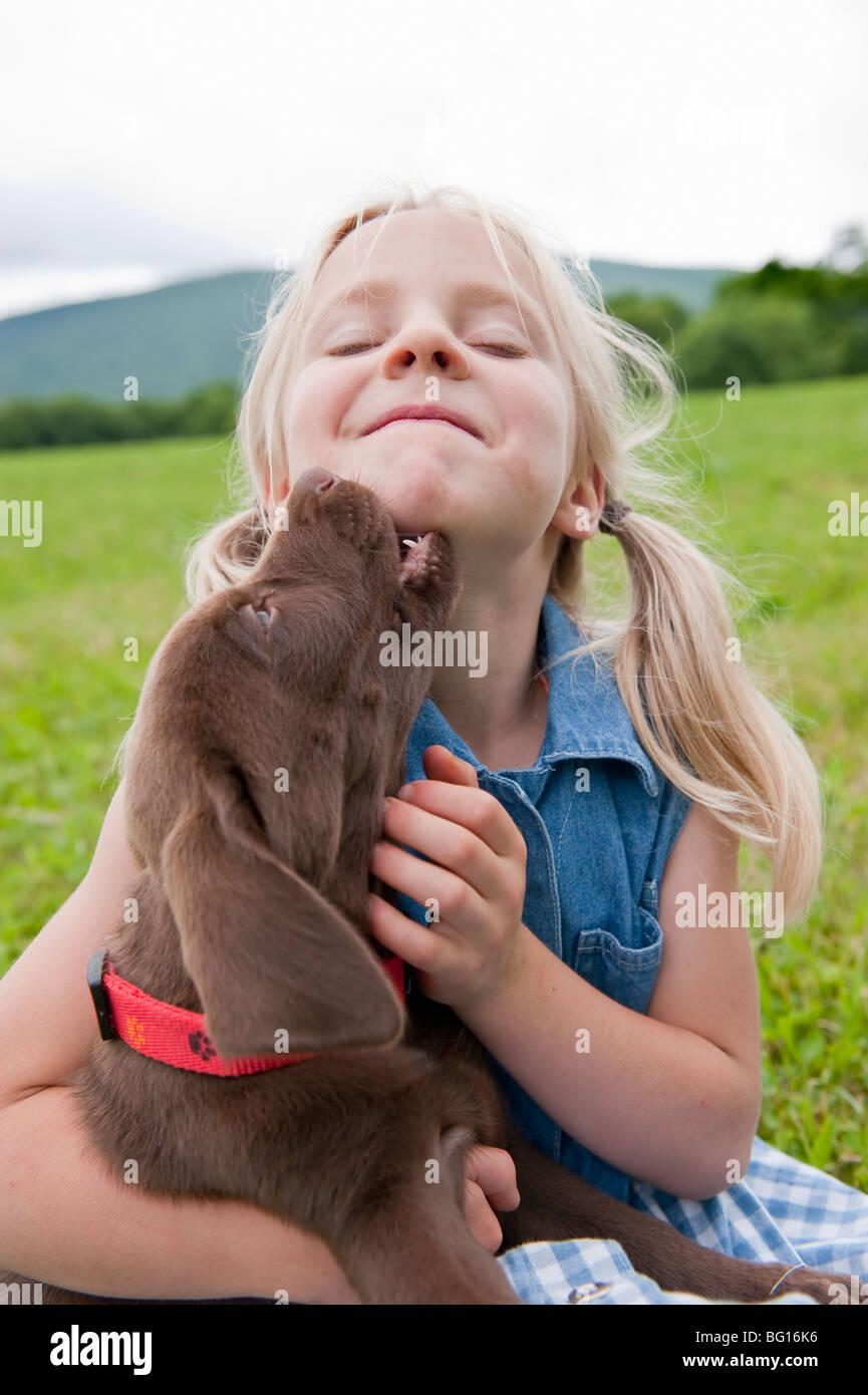 Junges Mädchen umarmt ihr Welpe Stockbild