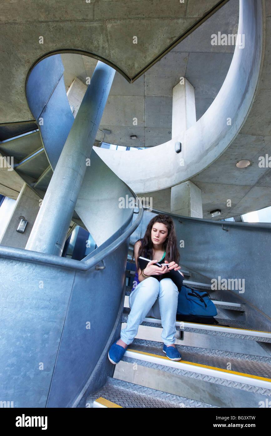 Studenten lesen auf Treppe Stockbild